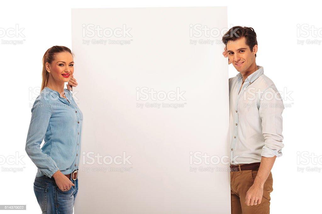 couple posing holding a white billboard stock photo
