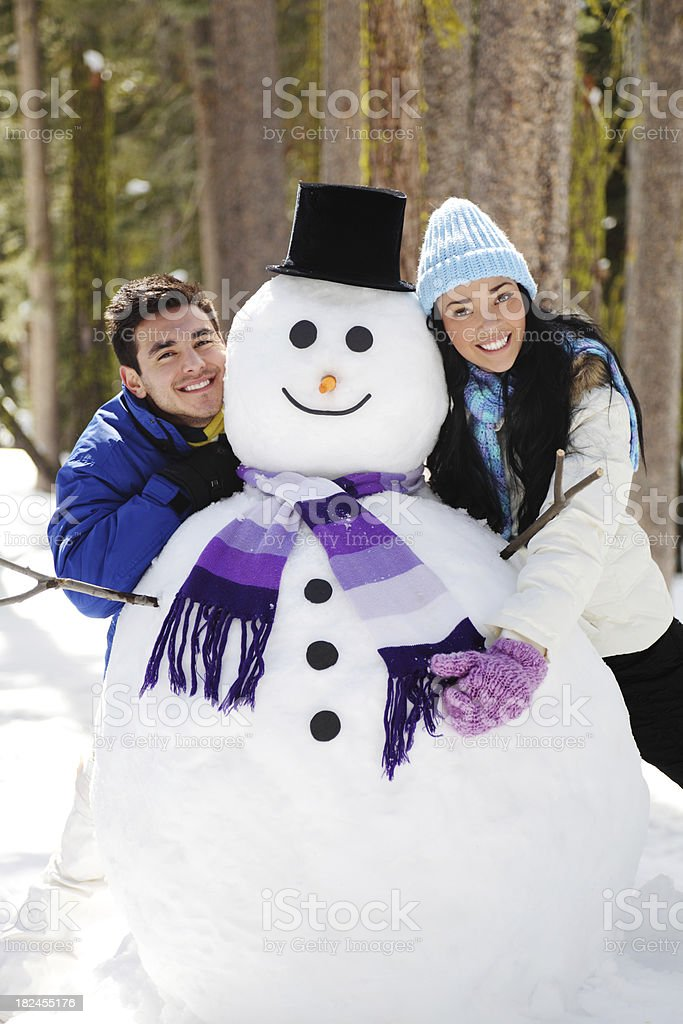 Couple posing with a cute snowman royalty-free stock photo
