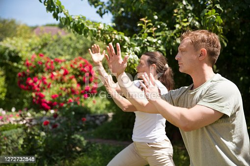 Couple practice Tai Chi Chuan in a park.  Chinese management skill Qi's energy. solo outdoor activities. Social Distancing