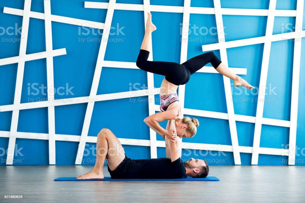 Couple practicing acro yoga in a studio. Couple yoga class stock photo