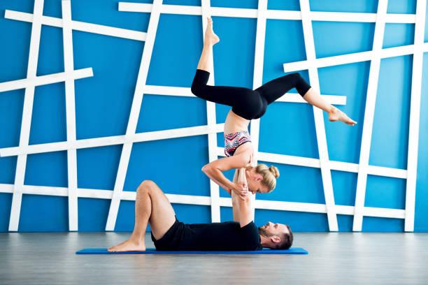 Couple pratique l'yoga acro dans un studio. Cours d'yoga de couple - Photo