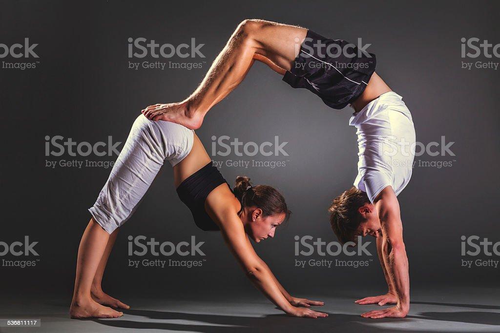 Couple practicing acro yoga stock photo