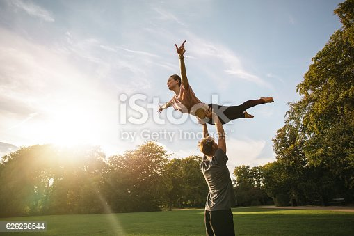 istock Couple practicing acroyoga at park 626266544