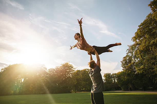 Couple practicing acroyoga at park - Photo