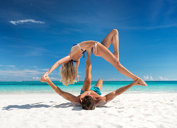 Couple practicing Acroyoga at the Beach - Photo
