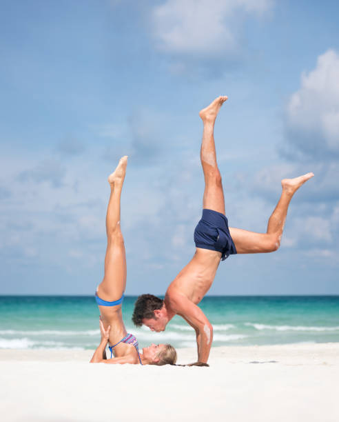 Couple practicing AcroYoga at the Beach Couple practicing AcroYoga at the Beach in an extreme pose. Man about to give his woman a kiss. Nikon D810. Converted from RAW. shoulder stand stock pictures, royalty-free photos & images