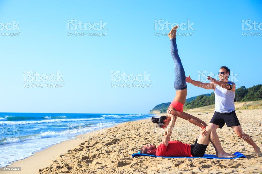 Couple practicing acroyoga  on beach stock photo