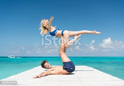 istock Couple practicing Acro-Yoga on Vacation 628934434