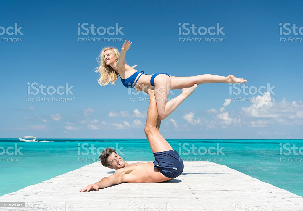 Couple practicing Acro-Yoga on Vacation - Photo
