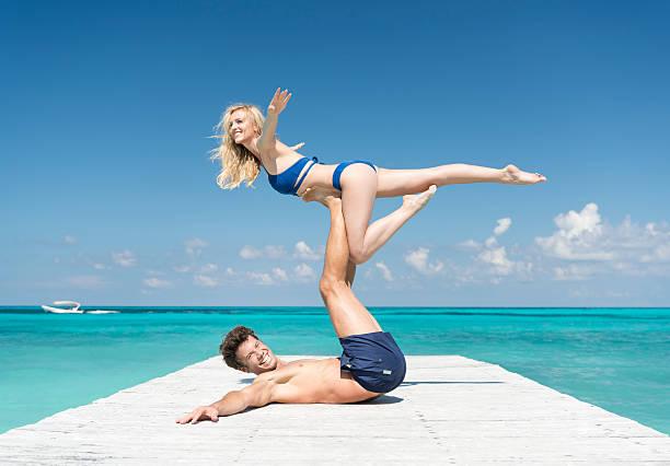 Couple practicing Acro-Yoga on Vacation - Photo