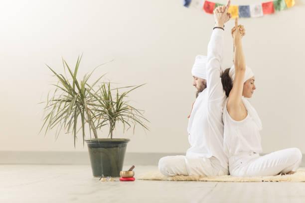 paar kundalini yoga üben und meditieren rücken an rücken - kundalini yoga stock-fotos und bilder