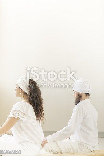 1060280760istockphoto Couple practicing Kundalini yoga lotus pose and meditation 964972100