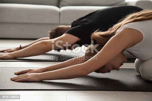 916126642istockphoto Couple practicing yoga in child pose relaxing on mat together 916126634
