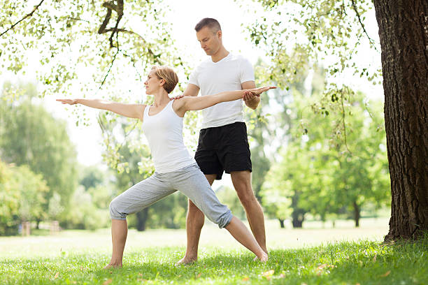 Couple practicing yoga in the park stock photo