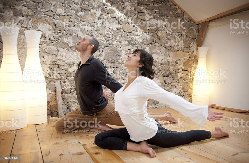 Couple practicing yoga on wooden floor with warm lighting royalty-free stock photo