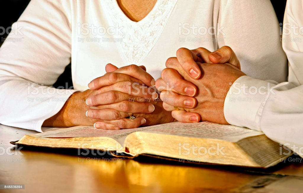 Couple Praying with Holy Bible A married couple wearing white shirts clasp their hands in prayer together over an open Holy Bible.  Main focus point is on the woman's hands. Adult Stock Photo