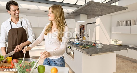 Young couple prepairing a healthy salad in a modern luxurious interior