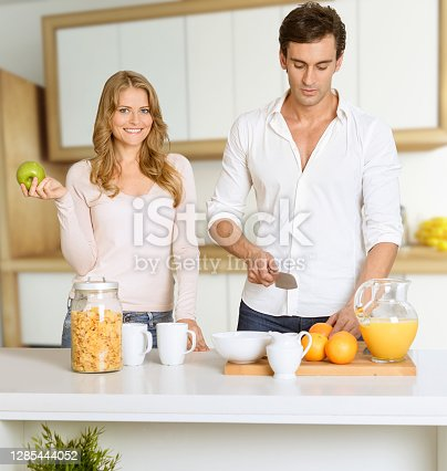 Young couple prepairing a healthy breakfast in a modern luxurious interior