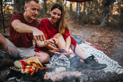 couple preparing a food in nature, campfire