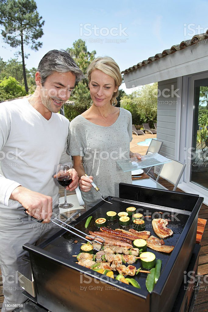 Couple preparing barbecue for dinner on sunny day royalty-free stock photo