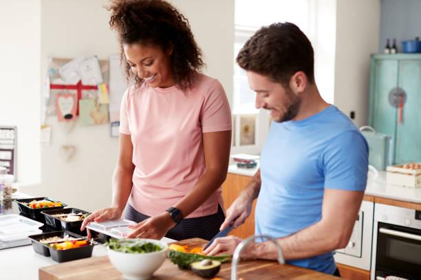 koppel bereidt batch gezonde maaltijden thuis in de keuken samen - mid volwassen koppel stockfoto's en -beelden