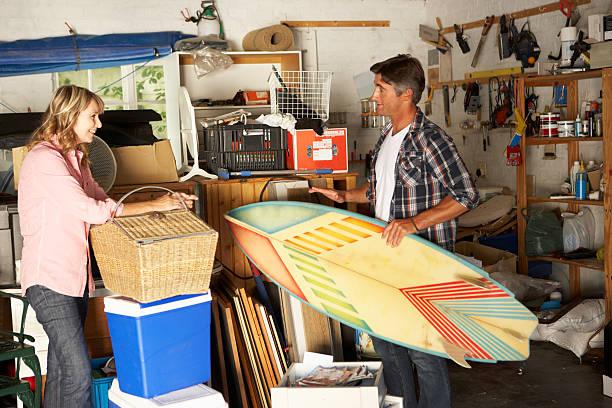 couple preparing food and surfing board for beach holiday - surf garage bildbanksfoton och bilder