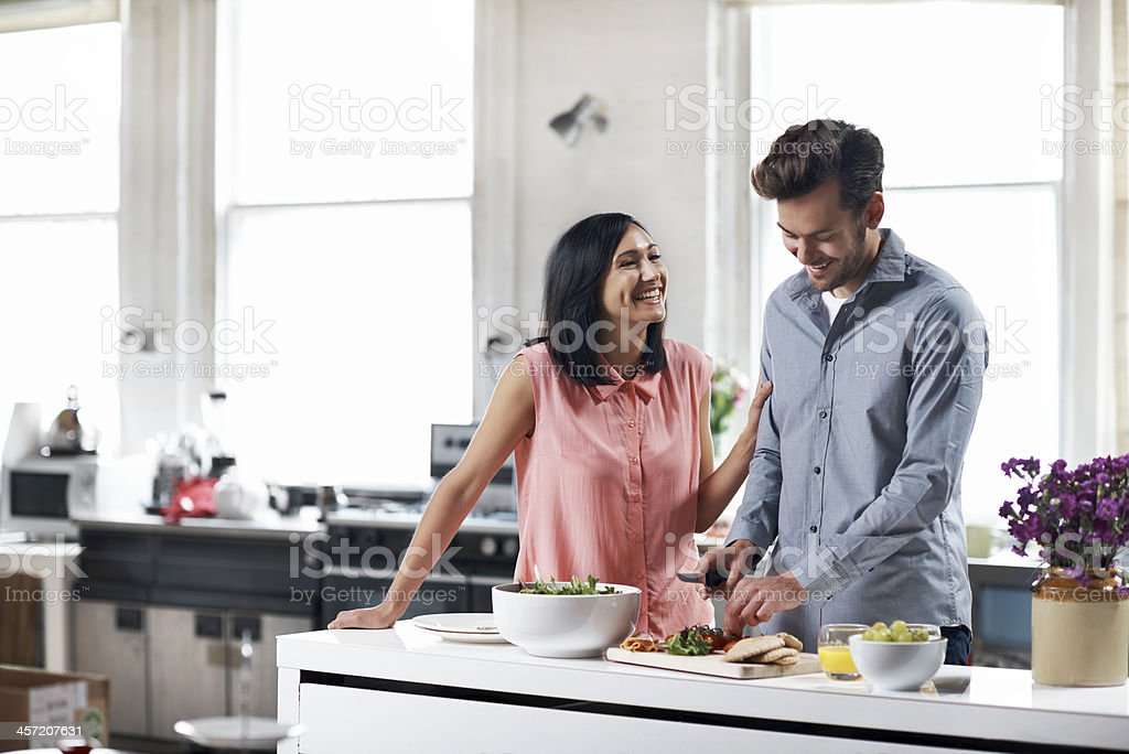 Couple preparing food in kitchen stock photo