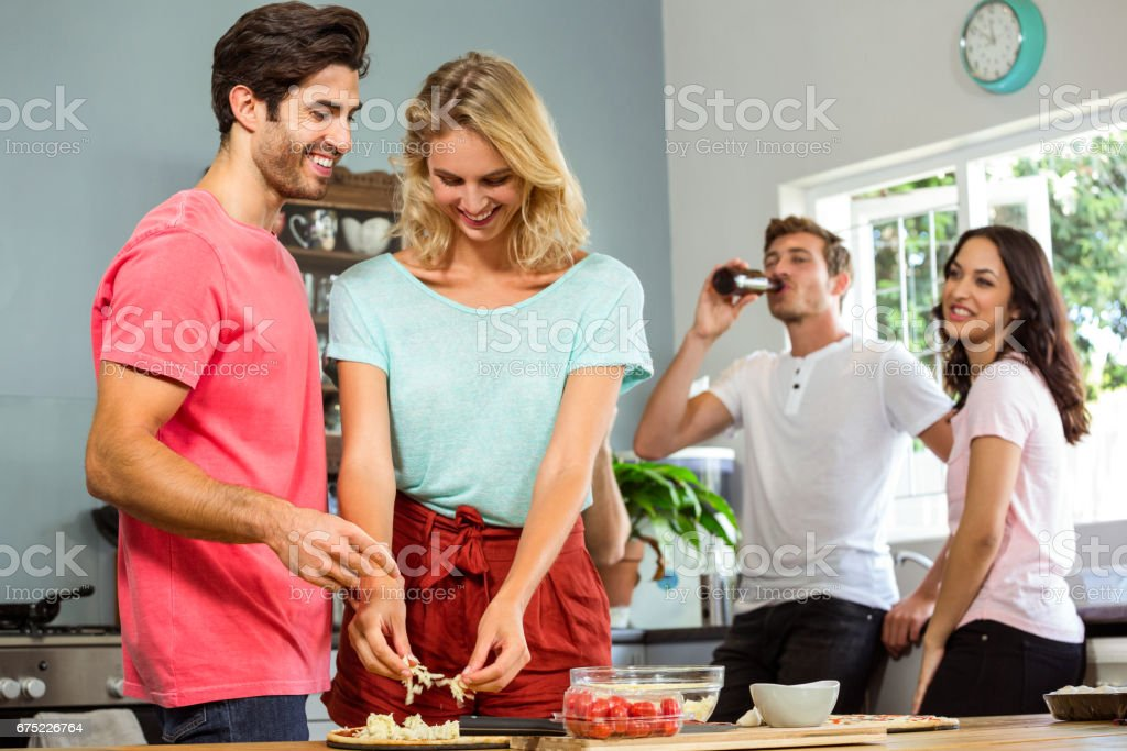 Couple preparing food while friends in background royalty-free stock photo