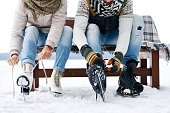 Unrecognizable couple sitting on bench and tying ice skates outdoors in winter