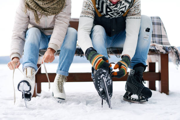 Couple preparing for ice skating Unrecognizable couple sitting on bench and tying ice skates outdoors in winter ice skating stock pictures, royalty-free photos & images