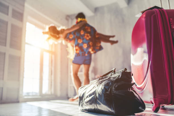 Couple preparing for travel Young romantic couple Is preparing for travel at home. Dancing in light modern room with suitcases standing nearby. honeymoon stock pictures, royalty-free photos & images