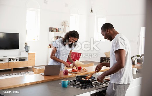 844050630 istock photo Couple Preparing Meal Together In Modern Kitchen 844050834