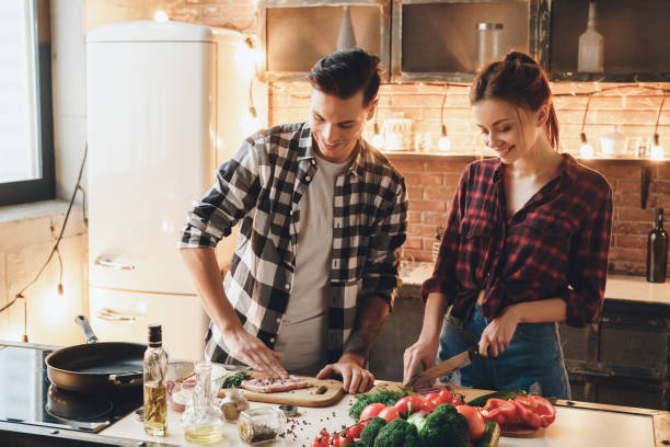 Couple preparing to receive guests cooking meat and salt stock photo