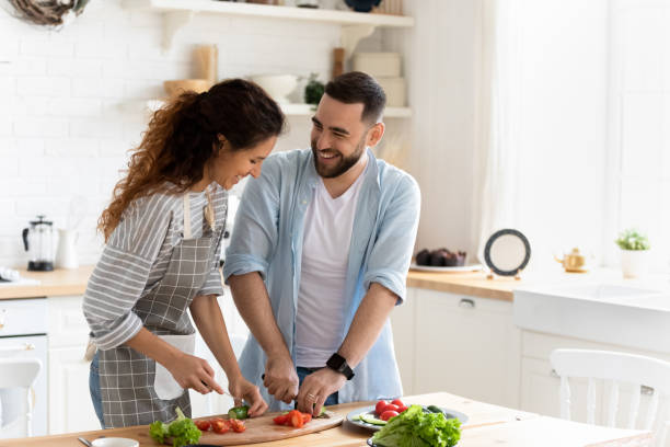 Couple preparing together vegetable salad standing in kitchen at home Happy couple standing in kitchen at home preparing together yummy dinner on first dating, spouses chatting enjoy warm conversation and cooking process, caring for health, eating fresh vegetable salad couple relationship stock pictures, royalty-free photos & images