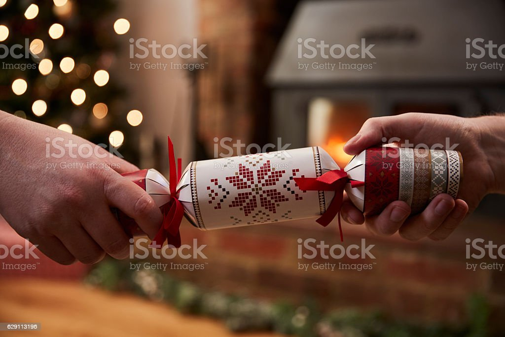 Couple Pulling Cracker In Room Decorated For Christmas stock photo