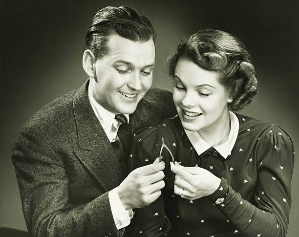 couple pulling wishbone in studio, (b&w), close-up, portrait - 1940s style stock photos and pictures