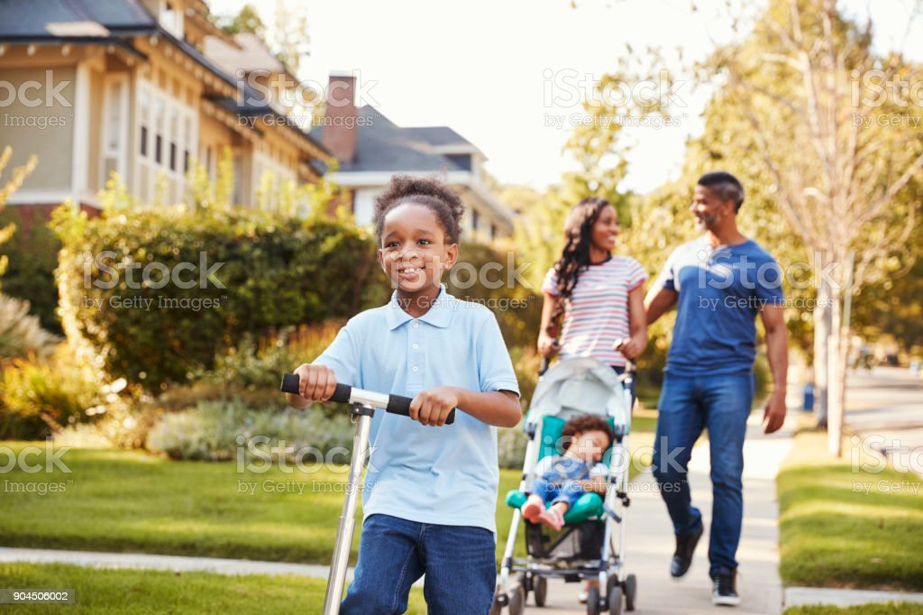 Couple Push Daughter In Stroller As Son Rides Scooter stock photo