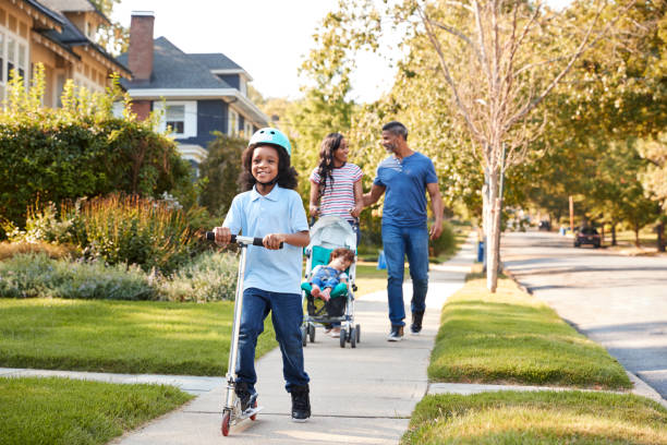 couple push daughter in stroller as son rides scooter - residential district stock pictures, royalty-free photos & images