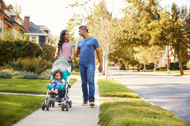 Couple Push Daughter In Stroller As They Walk Along Street Couple Push Daughter In Stroller As They Walk Along Street baby stroller stock pictures, royalty-free photos & images