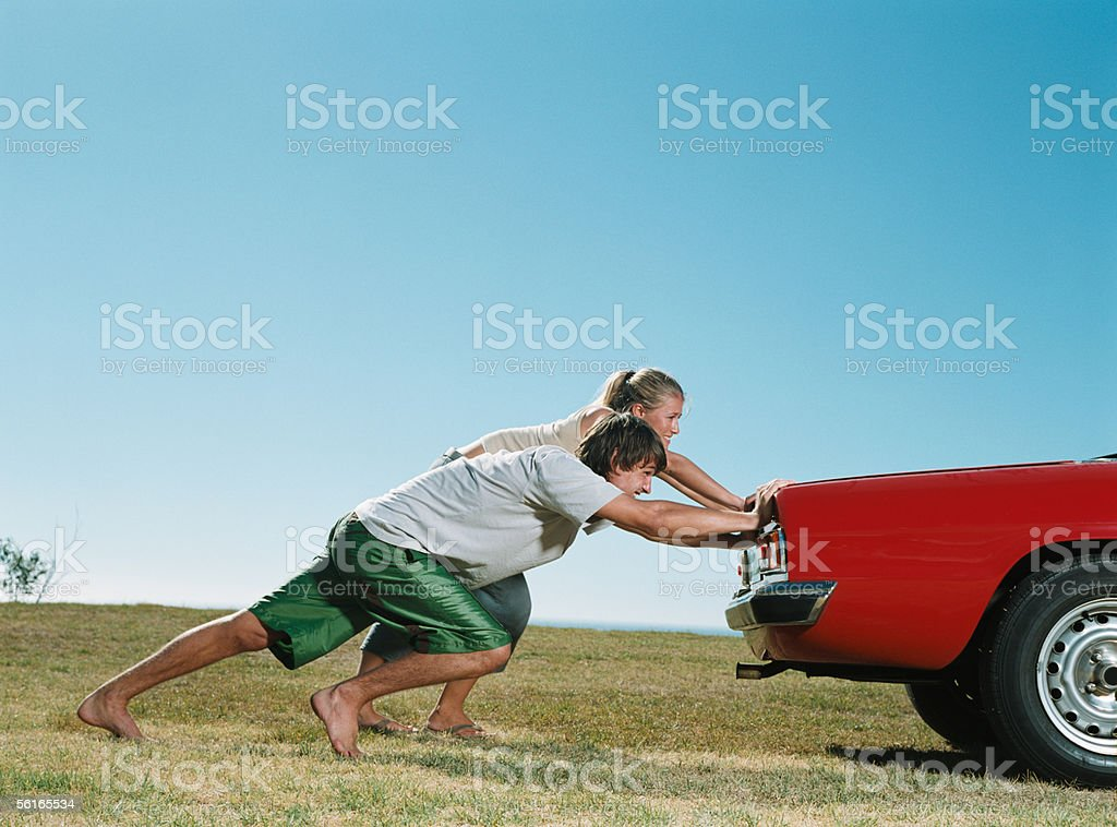 Couple pushing car stock photo