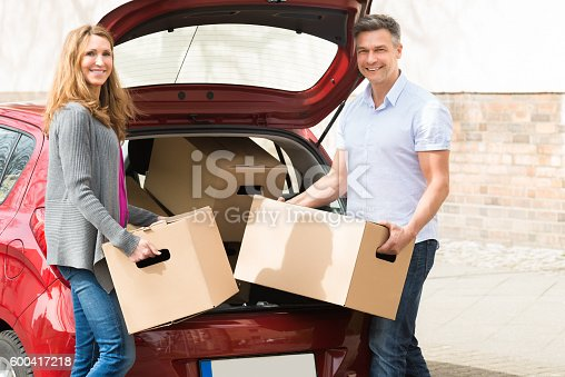istock Couple Putting Cardboard Box In Car Trunk 600417218