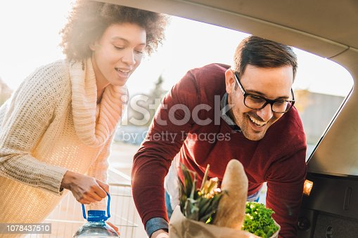 Happy couple packing shopping bags into a car