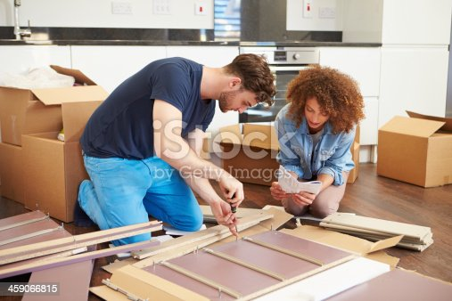 459373065 istock photo Couple Putting Together Self Assembly Furniture In New Home 459066815