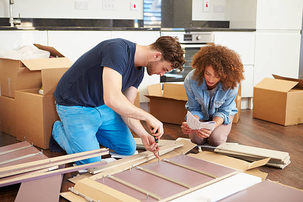 Couple Putting Together Self Assembly Furniture In New Home stock photo