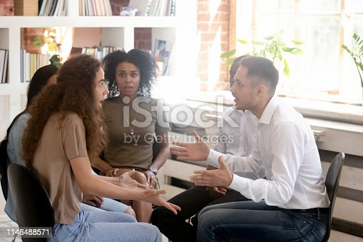 Multiracial people sitting on chairs at group rehab share personal problems struggle with addictions, focus on nervous couple girl guy quarrelling arguing bad relations enmity misunderstanding concept