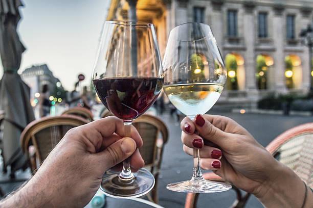 Couple raising glasses with wine Unrecognizable Couple raising glasses with red and white wine in Bordeaux - France bordeaux stock pictures, royalty-free photos & images