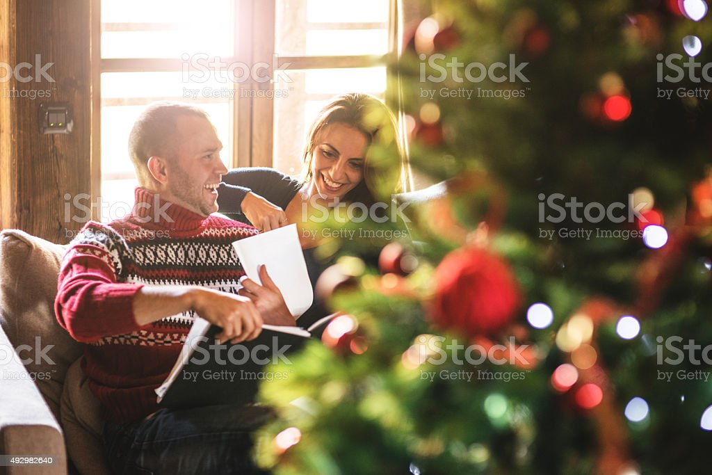 couple reading a book on christmas on the living room stock photo