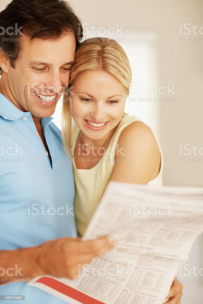 Couple reading a newspaper royalty-free stock photo