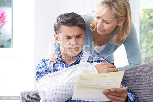 istock Couple Reading Letter About Husband's Injury 547129964