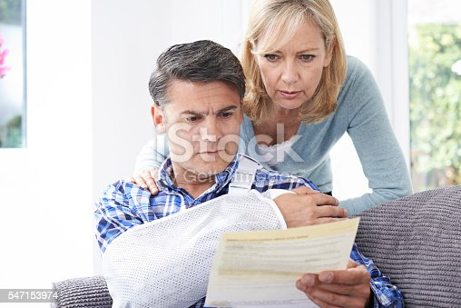istock Couple Reading Letter About Husband's Injury 547153974